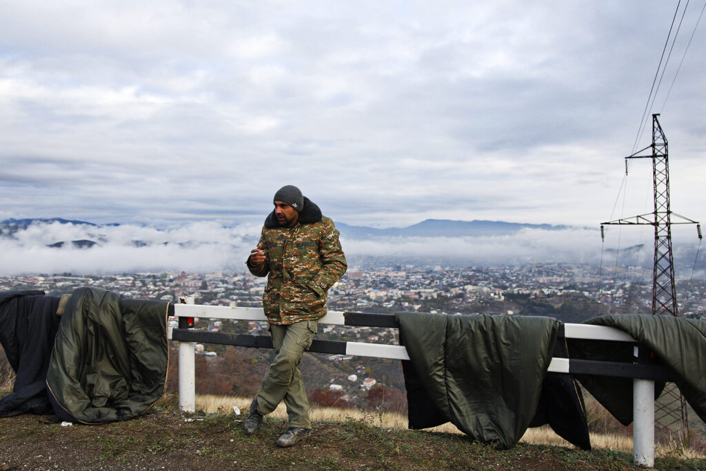 An ethnic Armenian soldier smokes by drying sleeping bags on a motorway in Nagorno-Karabakh. Photo Jack Losh
