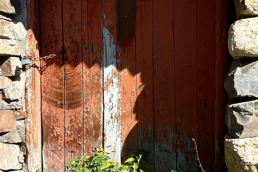 An old wooden door in partial shadow